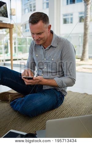 Smiling designer using smart phone while sitting on floor at office