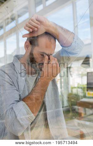 Tensed designer leaning on window seen through glass