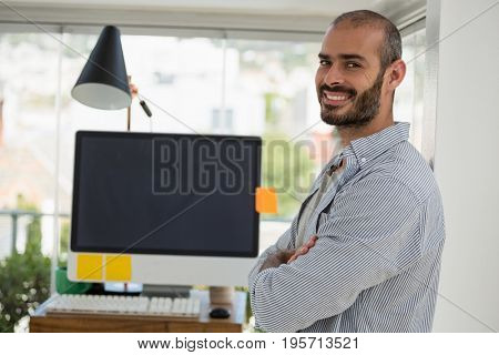 Side view portrait of designer with arms crossed standing in office