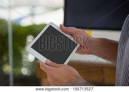 Cropped hands of designer using digital tablet computer at office