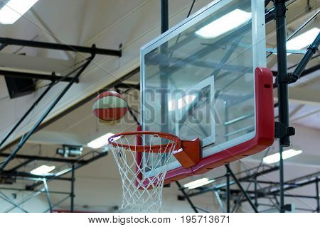 An orange and white basket ball bounces off of the rim of a basket in a n indoor gym