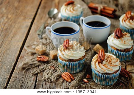 Carrot cinnamon cupcakes with pecan on a wood background