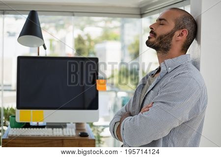 Designer with arms crossed relaxing while leaning on wall at office
