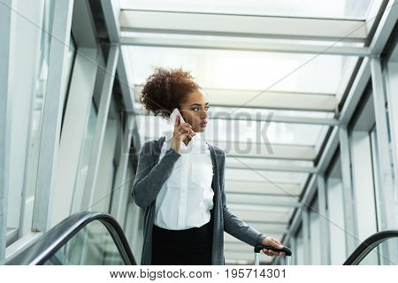 Entrepreneur woman talking on cell phone, standing on a escalator