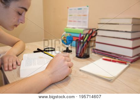 Young student Girl with lots of books studying for exams. Education concept