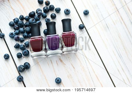 Bottles of nail polish on a white wooden table.