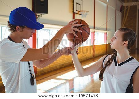 Male coach training female basketball player during practice in court