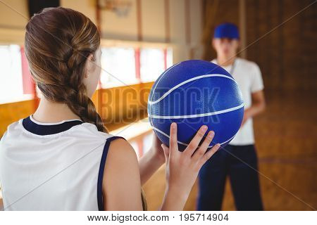 Female basketball player practicing with male coach in court