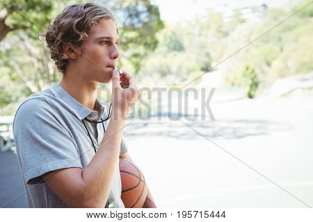 Man with basketball whistling while standing in basketball court