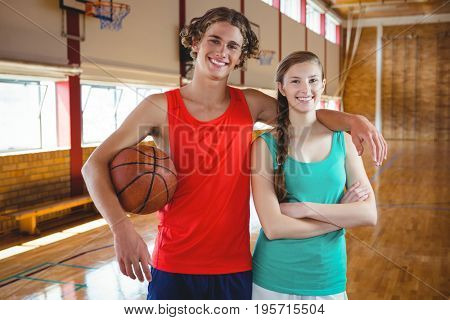 Portrait of basketball players with arm around standing in court