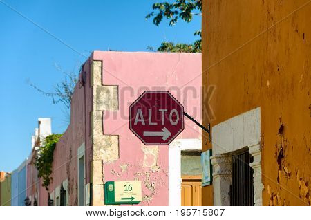 Stop sign on street corner with colorful colonial buildings in Campeche Mexico