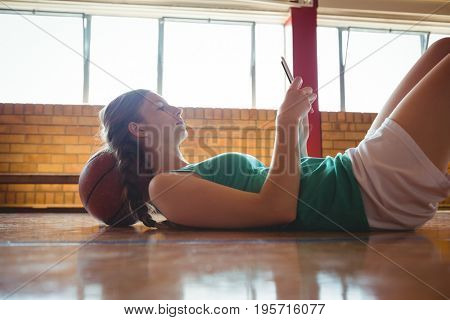 Side view of woman using digital tablet while lying on floor in basketball court