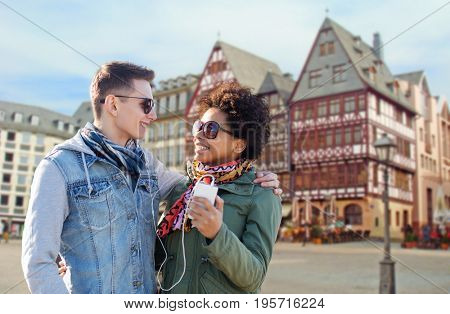 technology, people and travel concept - smiling couple with smartphone and earphones listening to music over frankfurt am main city street background