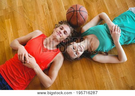 Overhead portrait of friends lying on floor in basketball court
