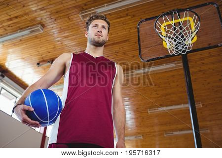 Thoughtful male basketball player with hand on hip standing by basketball hoop in court