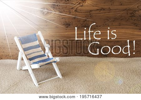Sunny Summer Greeting Card With Sand And Aged Wooden Background. English Text Life Is Good. Deck Chair For Holiday Or Vacation Feeling.