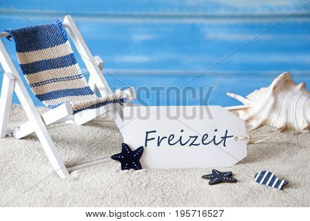 Summer Label With German Text Freizeit Means Leisure Time. Blue Wooden Background. Card With Holiday Greetings. Beach Vacation Symbolized By Sand, Deck Chair And Shell.