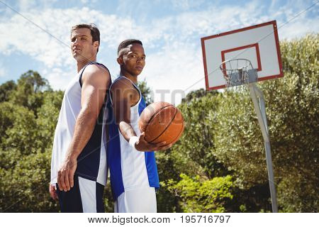 Portrait of basketball players standing back to back in court against sky
