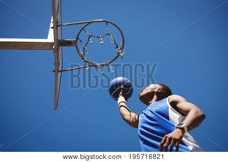 Low angle view of teenage boy playing basketball against clear blue sky