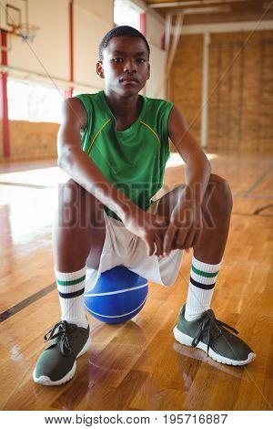 Portrait of teenage boy with hands clasped sitting on basketball in court
