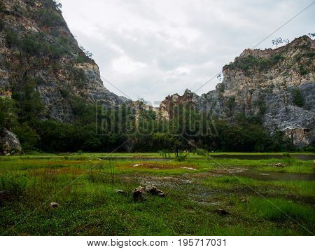 Wide-angle view of the curved craggy peaks of Khao Ngu Stone Park with a grassy wetland and trees in the foreground. Ratchaburi Thailand. Travel and environment concept.