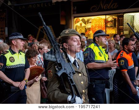 June 19 2017. A female soldier of the Spanish army marches with her rifle among policemen and the general public during Corpus Christi. Valencia Spain. Travel and celebration editorial concept.