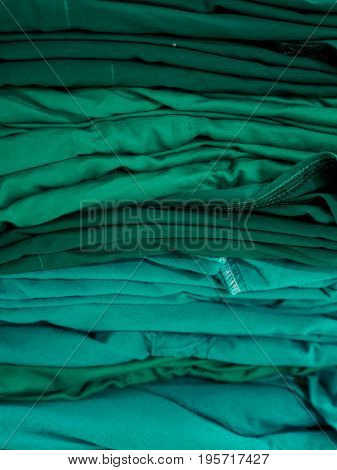 Close-up detail of a stack of green surgical gowns with autoclave sterilization. Vertical orientation. Healthcare and equipment concept.