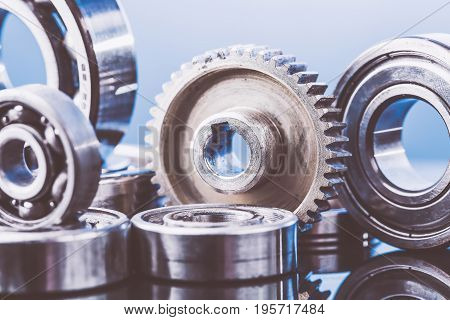 Group of various ball bearings and gears close up on nice blue background with reflections. Toned.