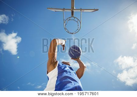 Directly below shot of basketball player taking a shot while playing in court against sky