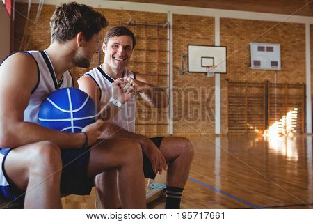 Happy basketball players doing fist bump while sitting on bench in court