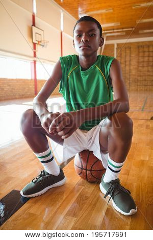 Portrait of teenage boy sitting on basketball in court