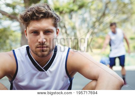 Portrait of confident male basketball player in court