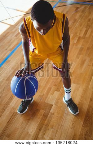 High angle view teenage boy practicing basketball in court