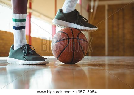 Low section of male teenager stepping on basketball while practicing in court