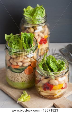 vegan couscous and pasta salad in mason jars with vegetables beans