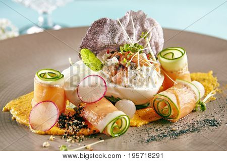 Restaurant Salad Food - Delicious Salad with Smoked Salmon and Burrata Cheese. Gourmet Restaurant Salad Menu. Salad Garnished with Greens and Vegetables