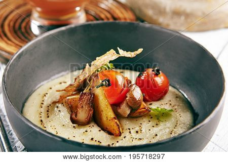 Restaurant Soup Food - Delicious Mushroom Soup with Garlic and Cherry Tomato. Gourmet Restaurant Soup Menu. Mushrooms Soup Garnished with Tea Broth and Garlic Mousse