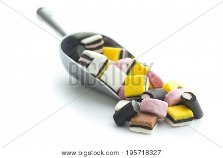 Mixed liquorice candies in scoop isolated on white background.