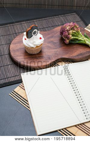 Table with white notebook and Variety of fresh vegetables, space for text on white.