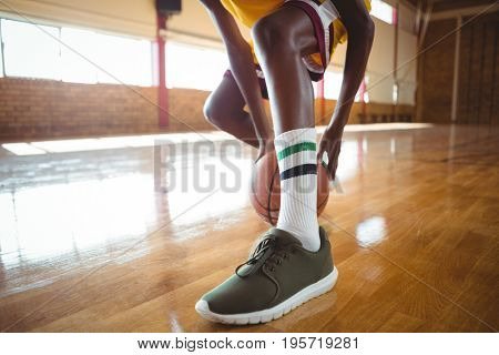 Low section of teenage boy practicing basketball in court