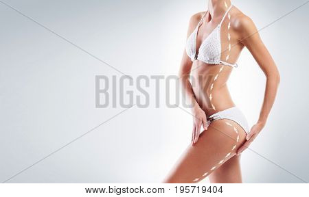 Beautiful, fit female body with drawing arrows on it. Health, sport, fitness, nutrition, weight loss, diet, cellulite removal, liposuction, healthy life-style concept.