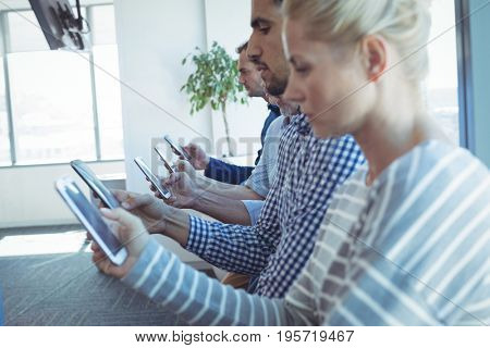 Business colleagues in row using mobile phones at office