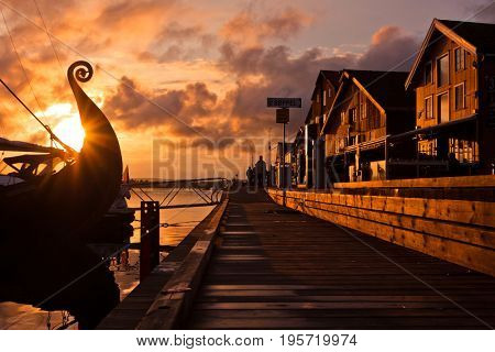 Seafront on the sunset with Viking ship