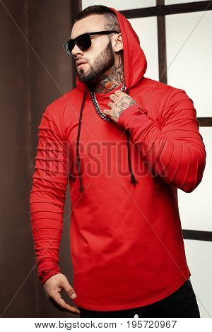Sexy closeup portrait of Elegant handsome male model with fashion tattoo and a black beard standing and posing for model tests or to journal in trend fashionable clothes. Professional Studio image.