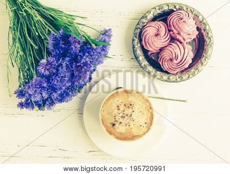 Pink zephyr marshmallow with cup of cappuccino coffee and bouquet of blue cornflowers on white wooden table. Top view.