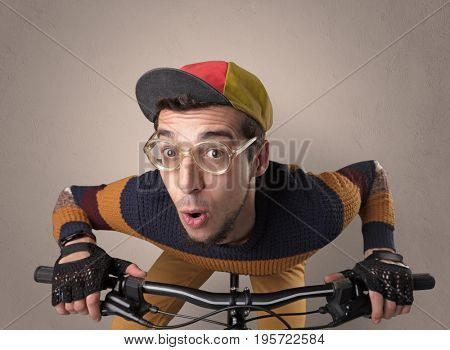 Nerd young foolish biker on a bike with oldschool outfit