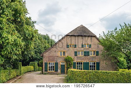 Abandoned thatched monumental farm with green shutters in a small village in the Netherlands. The farmhouse was built in 1850.