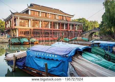 Suzhou, China - Nov 5, 2016: Classic building, bridge and boats near the entrance to the historic Zhouzhuang Water Town attraction.