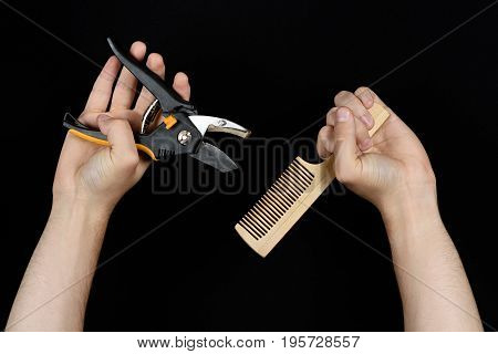Extraordinary Barber. Male Hands Holding Shears And Comb Isolated On Black Background From Down Side
