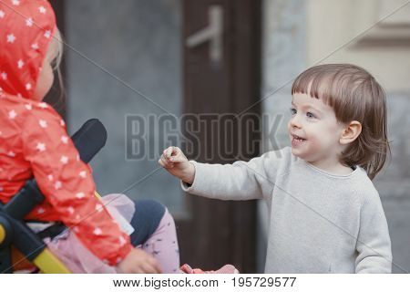 Happy Kid With Long Blond Hair Playing With A Little Girl Sitting In A Baby Stroller